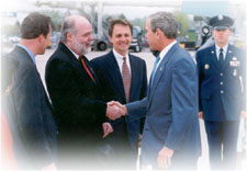 Dennis Shaw greeting President George W. Bush at steps of Air Force One. Gary Arneson is at Shaw's right and Rep. Mike Huebsch is on Shaw's left.